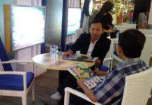 Sales perumahan saat menjelaskan produknya kepada calon pembeli di sebuah pameran perumahan.