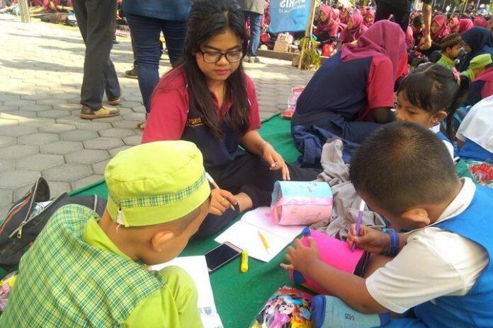 Mahasiswa UPGRIS membantu siswa TK membuat celengan dari barang bekas, Selasa (17/9).
