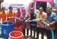Bupati Grobogan Sri Sumarni mengisi jeriken milik warga yang antre mendapatkan air bersih di Kecamatan Kradenan, Selasa (24/9).