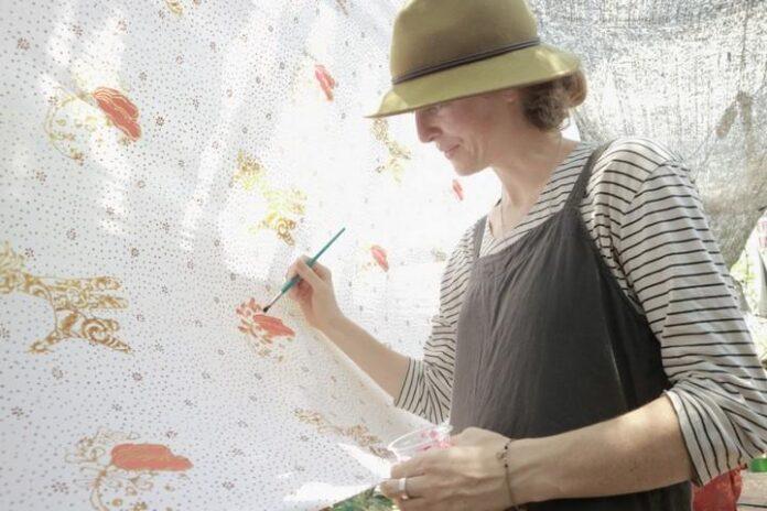 Seorang turis ambil bagian melukis di kain sepanjang 100 meter di Kampung Batik, Rabu (2/10).