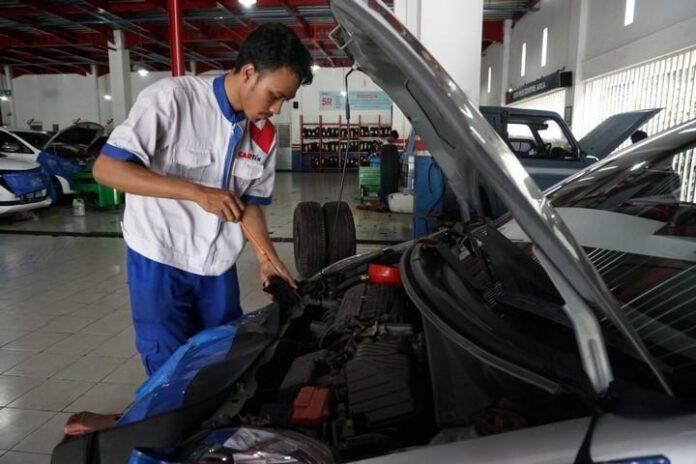 Seorang mekanik di CARfix sedang melakukan perawatan berkala terhadap mobil pelanggan.