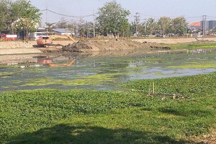 Sebuah ekskavator sedang melakukan pengerukan sedimentasi di Kanal Banjir Barat.