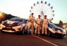 Tiga dari empat pebalap Team CARfix Indonesia pose di depan dua mobil.