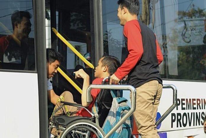 Penyandang disabilitas dibantu untuk naik ke bus khusus.