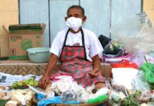 Pedagang sayuran memakai masker