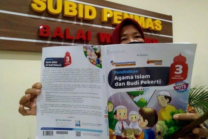 Perwakilan dari Forum Wali Murid Jateng menunjukkan buku pelajaran yang berisi ujaran kebencian, Senin (15/2).