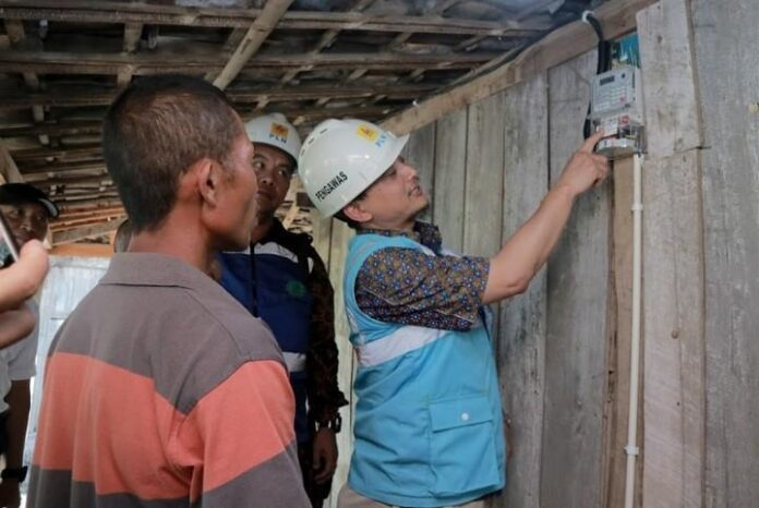 Petugas PLN saat melakukan penyambungan listrik gratis kepada masyarakat kurang mampu.