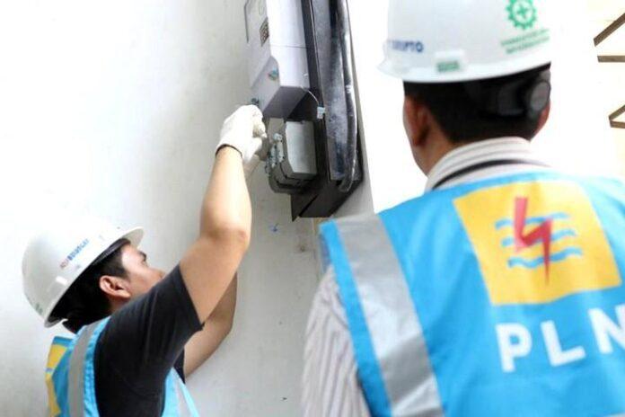 Petugas dari PLN memeriksa sambungan meteran
