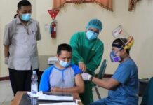 Seorang guru mendapatkan vaksinasi